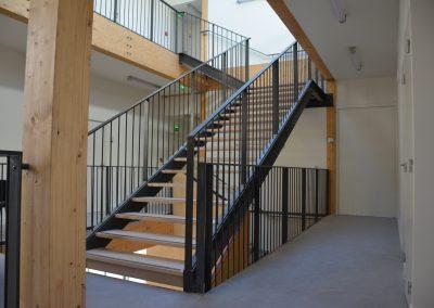 Escalier droit à marches en bois et garde-corps à barreaux en acier