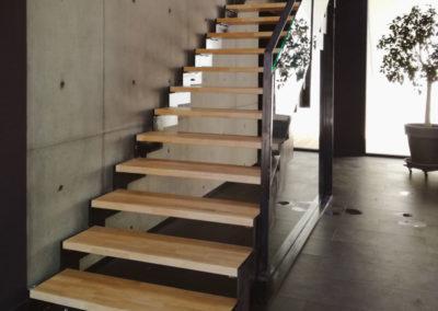 Escalier droit en acier et aux marches en bois avec garde-corps en verre