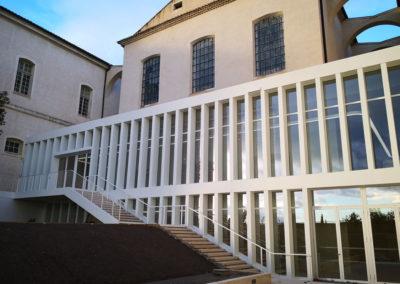 Extension en ossaure légère acier avec baie vitrée grande hauteur et escalier métallique