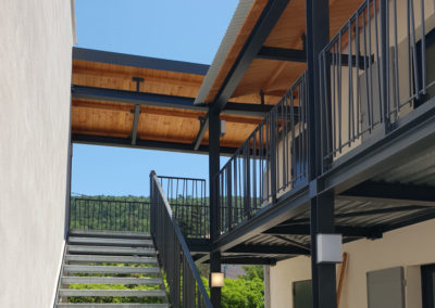 Passerelle extérieure avec garde corps à barreaux acier croisés et auvent métal et bois