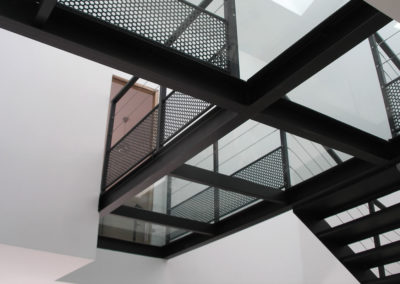 Passerelle intérieure en acier avec platelage en verre et garde-corps à fils