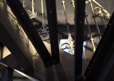 Détail du garde-corps en fonte d'escalier vu au travers des marches