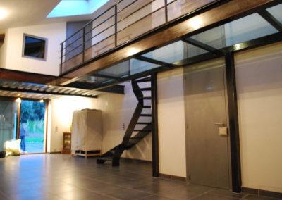 Passerelle d'intérieur en verre et métal avec escalier métallique tournant