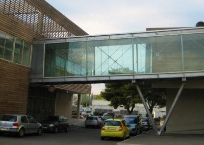 Passerelle extérieure couverte en verre et métal posée sur poteaux